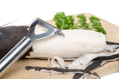 Black radish, parsley and a peeler on a wooden cutting board. Isolated on white Royalty Free Stock Photos