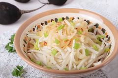 Black radish salad with fried onions in bowl Stock Image