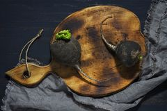 Black radish on wooden board. Black radish on a wooden board, top view Stock Images
