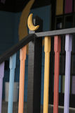 Black Railing with Moon 2. Black Railing with Moon accent. Railings have yellow, orange, blue and purple colors with colorful porch stock photo