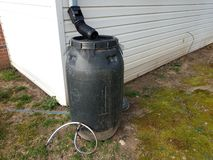 Black rain barrel with gutter downspout and hose. And white house stock photos