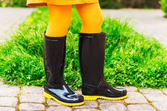 Black rain boots on child's feet Royalty Free Stock Images