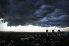 Black rain clouds in sky above homes royalty free stock photos