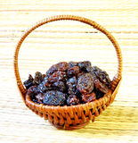 Black raisin in wicker basket on matting Royalty Free Stock Photos