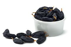 Black raisins  in cup on white background. Isolated Stock Images
