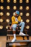 Black rapper in cap sitting on the steps