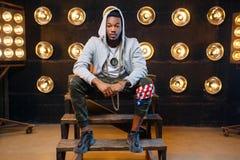 Black rapper in hoodie sitting on the steps