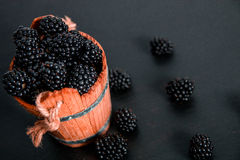Black raspberries in a wooden basket on   background. Frame. Copy space. Top view. Royalty Free Stock Photo