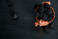 Black raspberries in a wooden basket on   background. Frame. Copy space. Top view. Stock Image