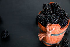 Black raspberries in a wooden basket on   background. Frame. Copy space. Top view. Royalty Free Stock Photography
