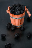 Black raspberries in a wooden basket and on  table. Copy space. Black raspberries in a wooden basket and on black wooden table Stock Photo