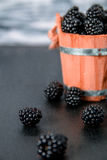 Black raspberries in a wooden basket and on   table. Copy space. Close up. Black raspberries in a wooden basket and on black wooden table. Copy space Royalty Free Stock Photos