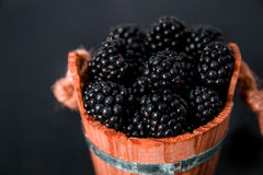 Black raspberries in a wooden basket and on   table. Copy space. Close up. Black raspberries in a wooden basket and on black wooden table. Copy space. Close up Royalty Free Stock Photos