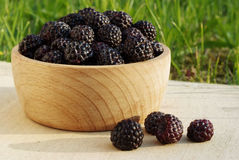 Black raspberries in the wooden cup. Fresh juicy black raspberries in the wooden cup Royalty Free Stock Images