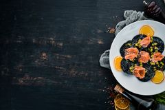 Black ravioli with salmon and parmesan cheese. In a plate on a wooden background. Top view. Free copy space stock images