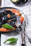 Black ravioli with salted salmon Stock Images