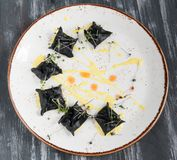 Black ravioli with seafood. On a plate top view. On wooden black background. royalty free stock photo