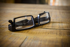Black reading glasses on a wooden table.  stock images