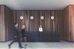 Black reception desk, wooden office, people Royalty Free Stock Images