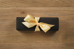 Black rectangle gift box with champagne color ribbon bow on wooden oak table from above Royalty Free Stock Photography