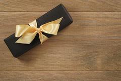 Black rectangle gift box with champagne color ribbon bow on wooden oak table from above. Top view royalty free stock photography