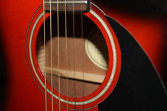 Black red  acoustic guitar closeup. On the strings Stock Photos
