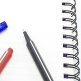 Black red and blue pen with notebook isolated on white Royalty Free Stock Image