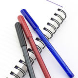 Black red and blue pen with notebook isolated on white Royalty Free Stock Photography