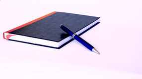 Black and Red Book with Blue Pen Stock Images
