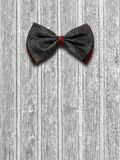 Black and red bow tie on a light wooden background Stock Photos