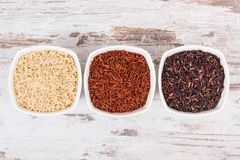 Black, red and brown rice in glass bowls, healthy nutrition concept Stock Photo