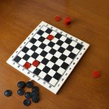 Black and red checkers on a game board. On a wooden background royalty free stock photography