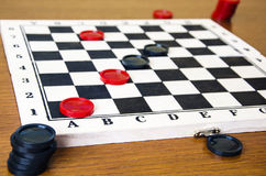 Black and red checkers on a game board. On a wooden background stock image