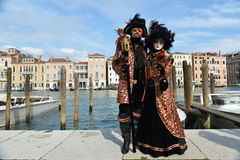 Black and red costumed couple. Standing at Salute in Venise Royalty Free Stock Photos