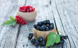 Black and Red Currants. Fresh ripe organic red and black currants with green leaf in a wooden bowl on the rustic wooden table. Closeup with copy space Stock Photo