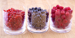 Black, red currants and raspberries in glasses. On wooden background Stock Images