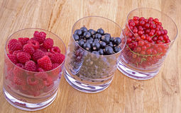 Black, red currants and raspberries in glasses. On wooden background Stock Photography