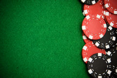 Black and red gambling chips on green background Royalty Free Stock Image