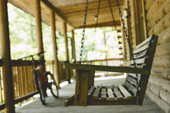 Black and Red Hard Tail Bike in the Back of a Brown Wooden Swing Chair Royalty Free Stock Images