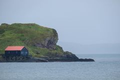 Black and red house. Coastal building on a rocky outcrop, Scotland Royalty Free Stock Photo