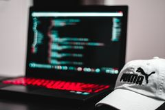 Black and Red Laptop Computer Beside White Puma Curve Brim Cap Stock Images