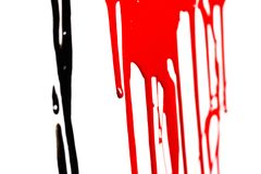 Black and red paint. Close-up of the black and red flowing paint isolated on white background royalty free stock images