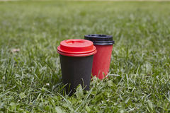 Black and red paper cups of coffee to takeaway on green grass lawn. Breakfast morning outside the cafe. Royalty Free Stock Photo