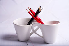 Black and red pencils stand in two cups Stock Images