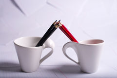 Black and red pencils stand in two cups Royalty Free Stock Photos