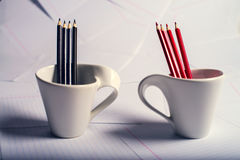 Black and red pencils stand in two cups Stock Photography