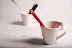 Black and red pencils stand in two cups Stock Photos