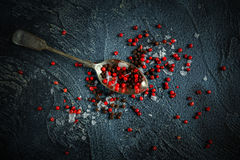 Black, red peppercorns mixed with salt on old rustic spoon. dark blue stone background. Royalty Free Stock Image
