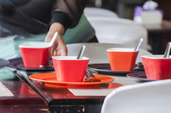 Black and red plates and cup, stainless fork and spoon Royalty Free Stock Photos