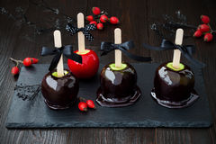 Black and red poison caramel apples. Traditional dessert recipe for Halloween party. Stock Photos